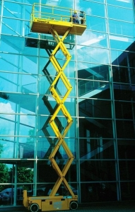 window cleaner using the scissor lift to clean an office window