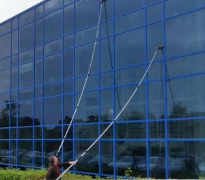 widow cleaner cleaning one of clients commercial windows